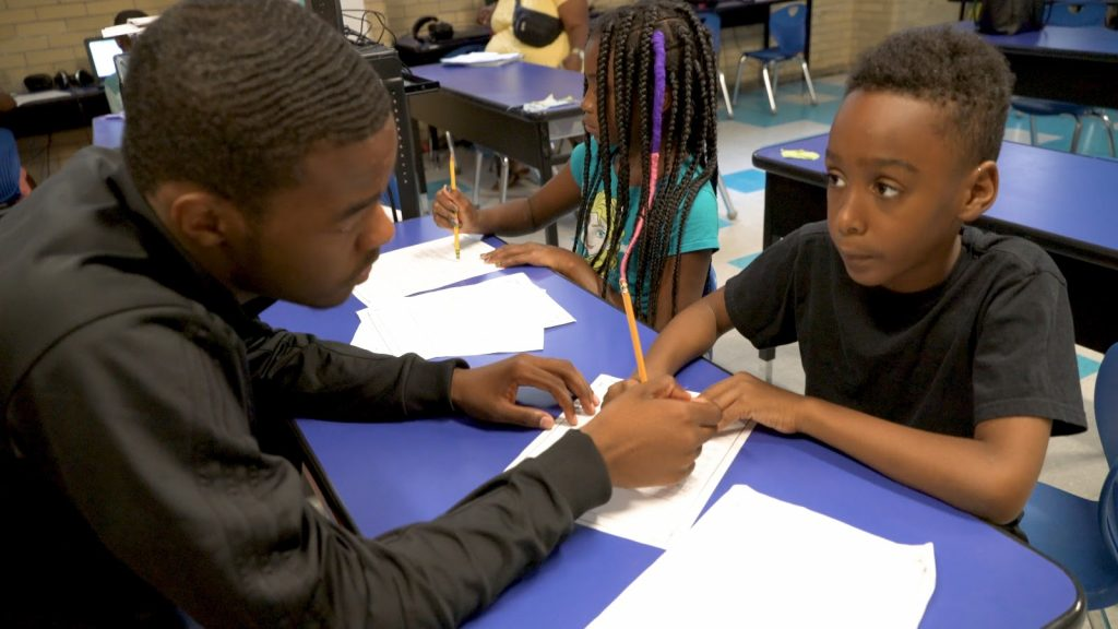 Black educator helping young Black student with school work in a classroom