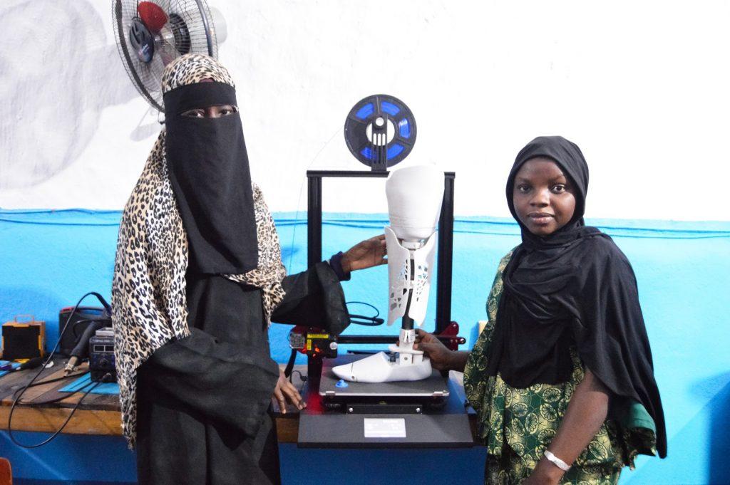 Duas mulheres africanas em frente a uma impressora 3D com um protótipo de prótese de perna
