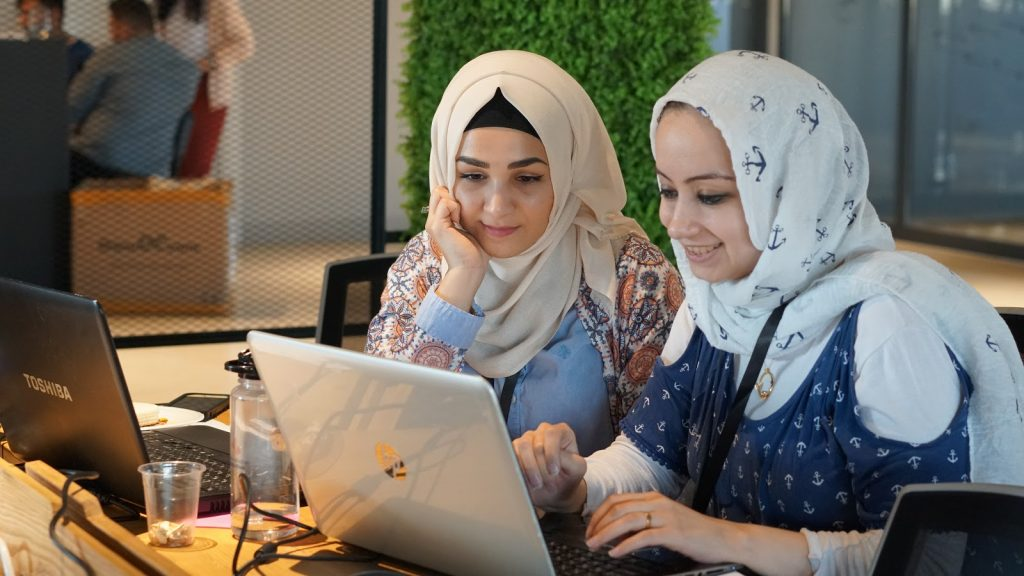 Two women with headscarves looking at a laptop