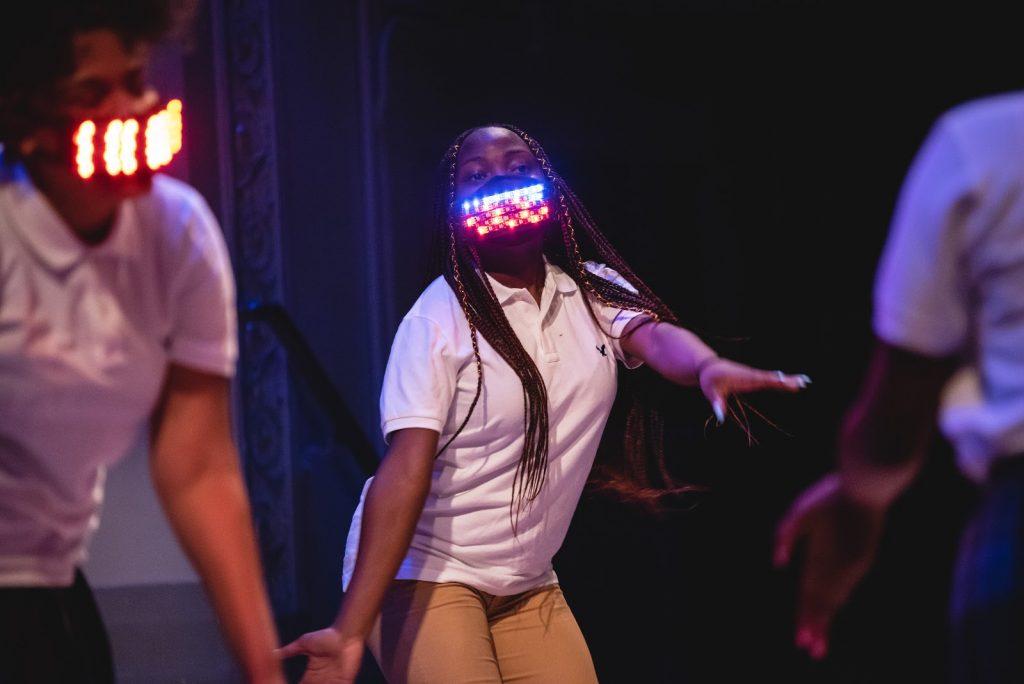 Grupo diversificado de meninas dançando e usando máscaras com luzes multicoloridas